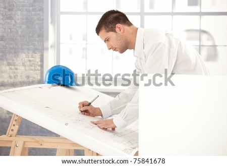 Young engineer busy by working, using drawing table.? - stock photo