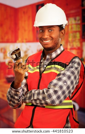 Young engineer carpenter wearing helmet, square pattern flanel shirt with red safety vest, holding small handheld electric saw smiling to camera