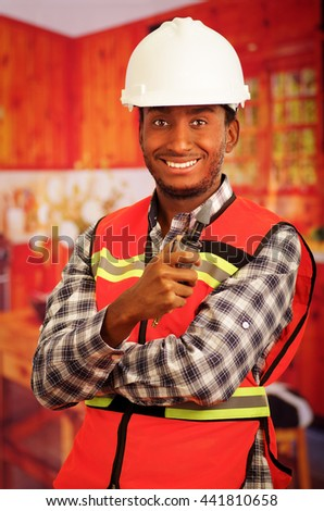 Young engineer carpenter wearing helmet, square pattern flanel shirt with red safety vest, holding small handheld electric polisher tool smiling to camera - stock photo