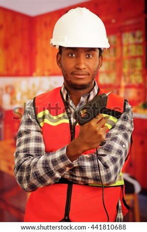 Young engineer carpenter wearing square pattern flanel shirt with red safety vest, holding glue gun smiling to camera - stock photo