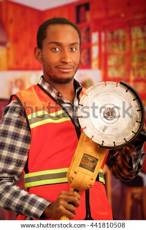 Young engineer carpenter wearing square pattern flanel shirt with red safety vest, holding handheld electric sander tool smiling to camera - stock photo
