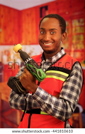 Young engineer carpenter wearing square pattern flanel shirt with red safety vest, holding handheld electric power drill smiling to camera - stock photo