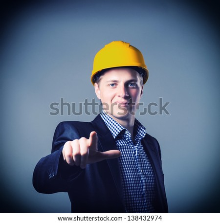 young engineer in a helmet shows the index finger - stock photo