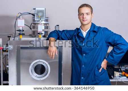 Young engineer in a scientific laboratory near the vacuum unit