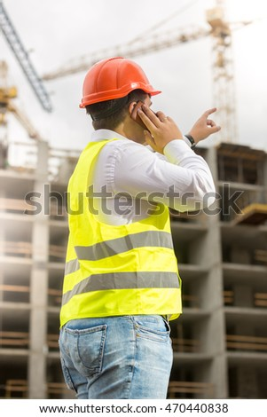 Young engineer in hardhat talking by phone and pointing at building site