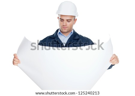 Young engineer looking at blueprint isolated on white background