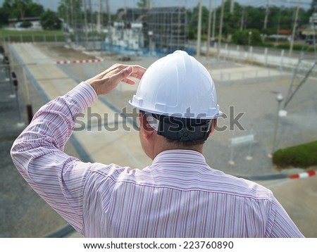 Young engineer looking work in front of construction site