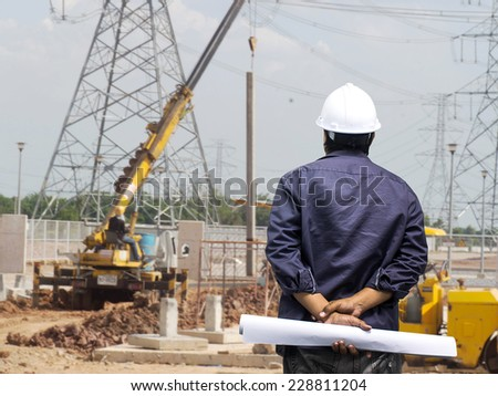 Young engineer looking work in front of construction site                  - stock photo