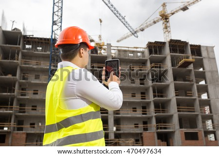 Young engineer on building site with digital tablet