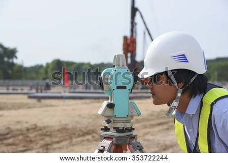 Young engineer surveyor working with theodolite at construction site - stock photo