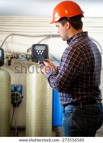 Young engineer taking meter readings from industrial pumps at factory - stock photo
