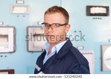 Young engineer wearing a safety glasses at control room - stock photo