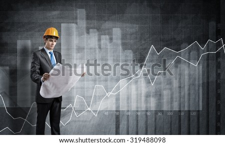 Young engineer wearing helmet with papers in hands and graphs at background - stock photo