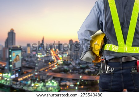 Young Engineer wearing yellow helmet Against the background the city - stock photo