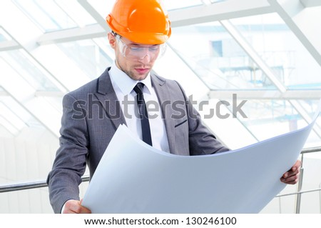 Young engineer with paper plans - stock photo