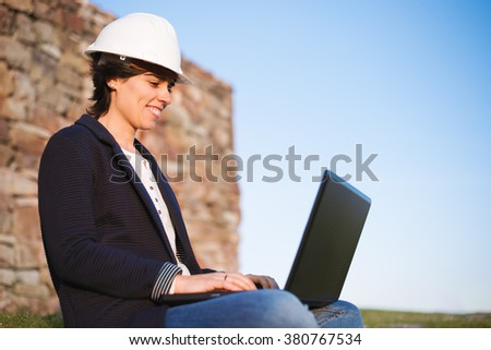 Young engineer woman entrepreneur working outdoor with laptop and safety helmet. Pioneer woman at work. Safety at work. - stock photo