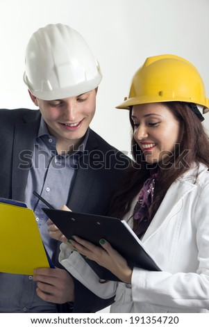 Young engineers studying plans for construction. In the studio. - stock photo