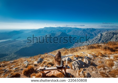 Young enjoying woman with raised hands on the top of a mountain, cheering elated and blissful  - stock photo