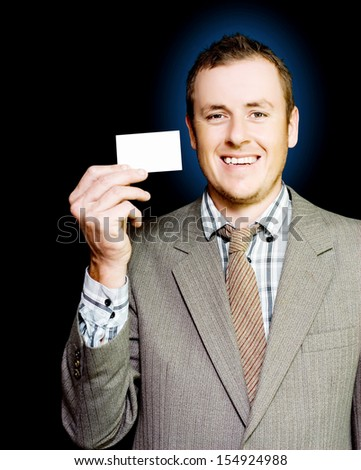 Young enthusiastic organised businessman holding up his blank busines card for attention as he strives to get his name , brand and style before the public eye in a branding concept - stock photo