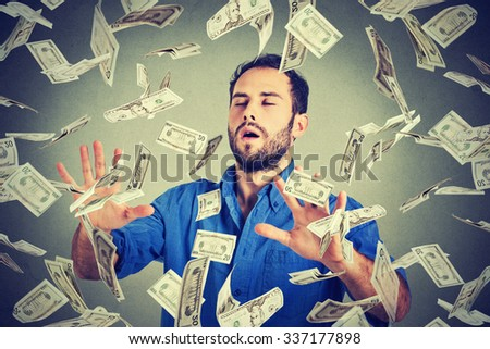 Young entrepreneur business man with eyes closed trying to catch dollar bills banknotes flying in air walking through money rain gray background. Financial corporate success crisis challenge concept - stock photo