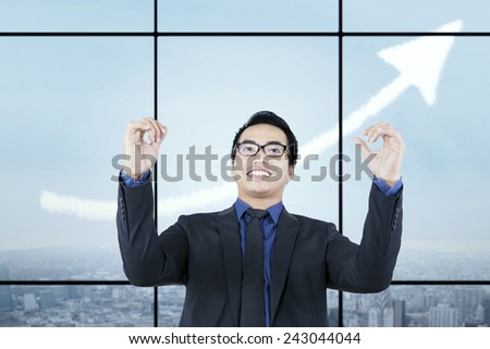 Young entrepreneur expressing his success with rise upward arrow on the sky - stock photo
