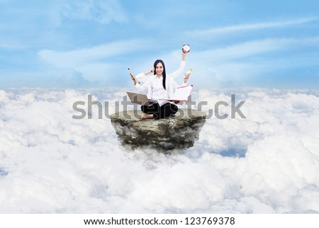 Young entrepreneur is doing multitasking above the clouds - stock photo