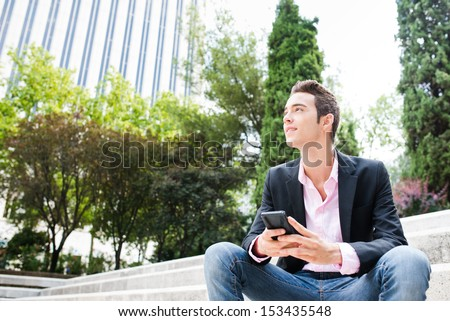 Young entrepreneur looking away and smiling sit on stairs. Focus on his face - stock photo