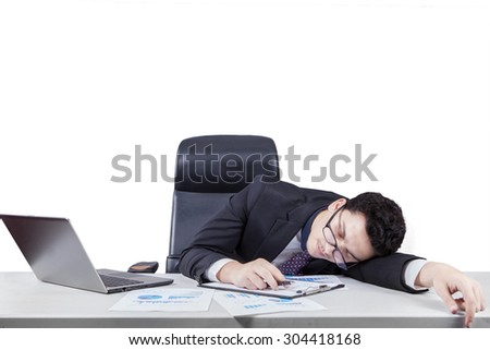 Young entrepreneur looks tired and sleeping on desk with laptop and business documents - stock photo