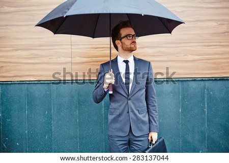 Young entrepreneur with briefcase standing outside under umbrella - stock photo