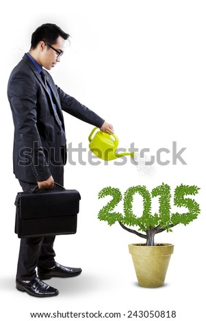 Young entrepreneur with briefcase watering a tree shaped number 2015, symbolizing investment for future - stock photo