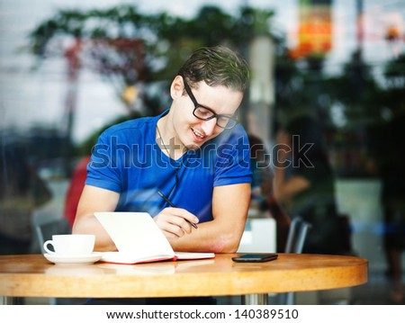 Young entrepreneur working in a cafe (soft focus) - stock photo
