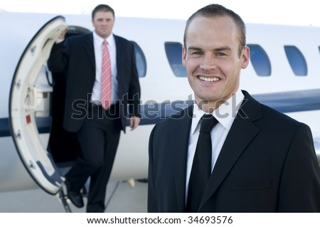 Young entreprenuers in front of their corporate jet - stock photo