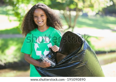 Young environmental activist smiling at the camera picking up trash on a sunny day - stock photo