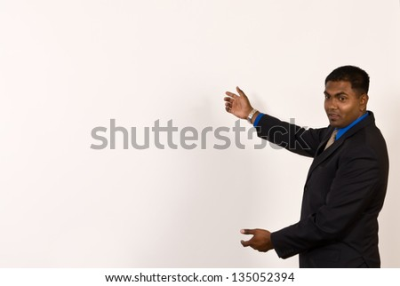 Young ethnic business man makes a gesture with his arms toward a large, blank off-white projector screen. The screen has been left blank for copy space. - stock photo