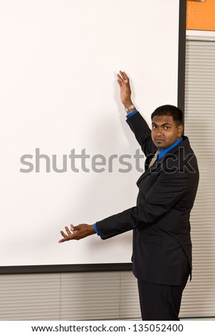 Young ethnic business man makes a gesture with his arms toward a large, blank off-white projector screen. The screen has been left blank for copy space.