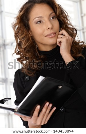 Young ethnic businesswoman on the phone, looking away, holding organizer.