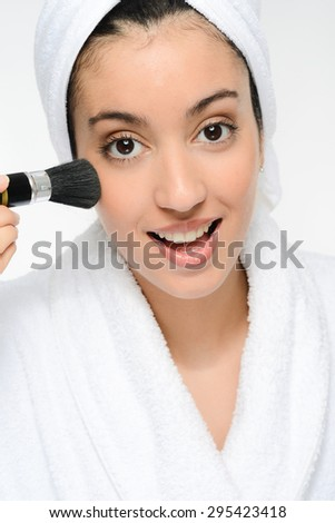 young ethnic woman in white peignoir putting on blush powder with a brush - stock photo