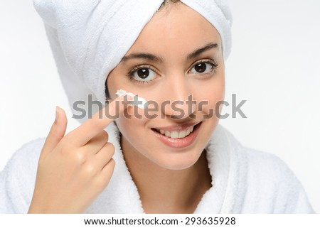 young ethnic woman in white peignoir putting on skincare facial cream - stock photo