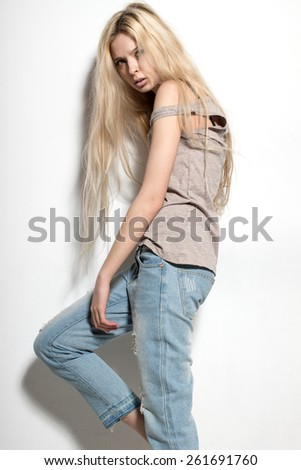 Young European attractive sexy fashion model with long blond natural hair, beautiful eyes, full lips, perfect skin is posing in jeans and shirt in studio for glamour vogue test photo shoot - stock photo
