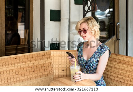 young european blond  woman with phone and sunglasses drinking lemonade in an cafe