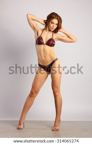 Young European fashion model woman with shiny healthy brunette hair, awesome gorgeous slim body and perfect skin, fitness bikini in studio for bodycare and wellness advertisement - stock photo