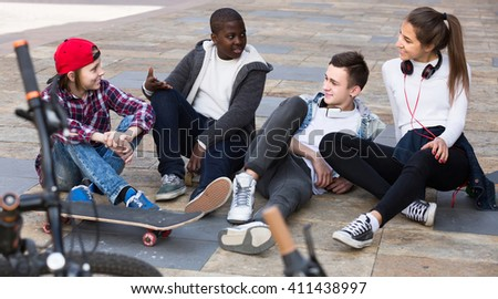 young european  girl and three boys hanging out outdoors and discussing something