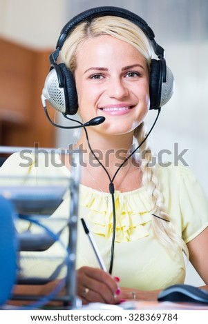 young european girl answering the call of technical support and smiling