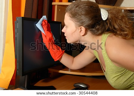 Young European girl wiping the dust from LCD monitor