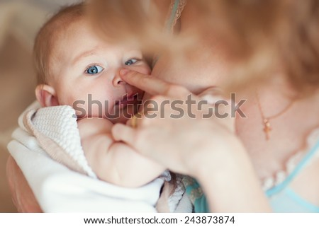 Young european mother holding her newborn baby on hands and breast feeding with adore. Baby look in camera - stock photo
