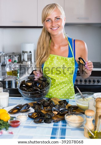 Young european woman cooking marinade for tasty mussels at kitchen table