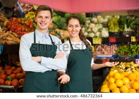 Young european workers selling fresh fruits and vegetables on market