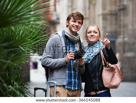 Young europenian couple sightseeing and taking pictures of city - stock photo