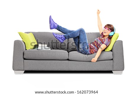 Young excited female listening music seated on a sofa isolated on white background - stock photo