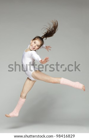 Young excited girl jumping in the studio